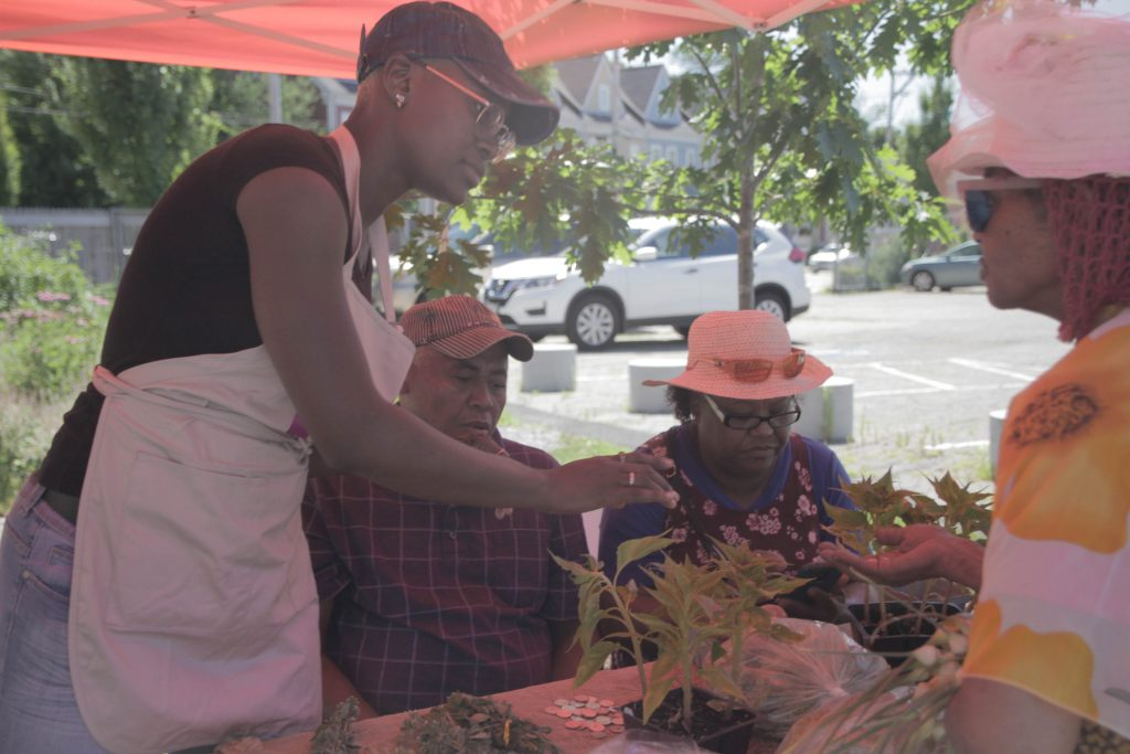 Jhane Thomas, WEHDC/Sankofa's Market Manager assists vendors Teo and Margarita at the Saturday Marketspace.
